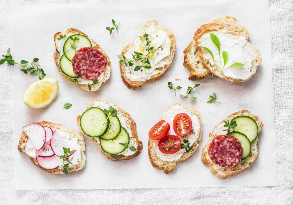 Variety of mini sandwiches with cream cheese, vegetables and salami. Sandwiches with cheese, cucumber, radish, tomatoes, salami, thyme, lemon zest on a light background, top view.